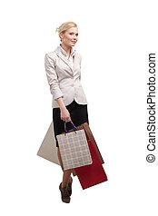 Attractive businesswoman in a light beige suit holding shopping bags