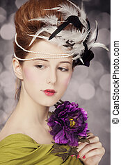 Redhead girl with Rococo hair style and flower at vintage background. Photo in old style.