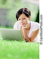 Girl lying on the green grass works at the laptop - Girl...