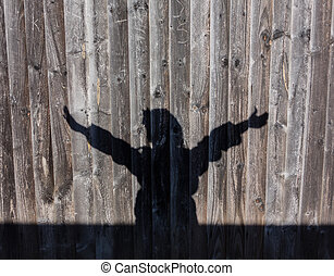 Hands up silouette wiht fence background