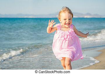 Little girl running on the beach - Little girl in pink dress...