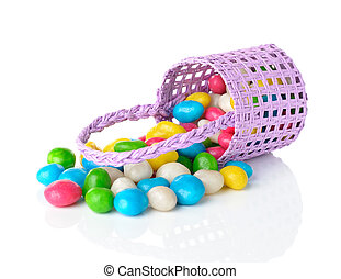 Colorful candy in a purple basket on white background