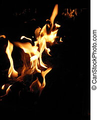 Flaming Fire - Orange flames in a fire pit with black...