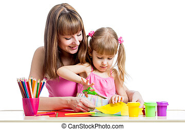 Mother teaches preschooler kid to do craft items DIY concept...