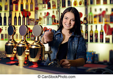 Bartender woman pours the beer into a glass