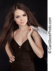 Beautiful woman with shopping bags isolated on black...