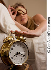 Shutting off the alarm clock - Blond woman sleeping in bed...
