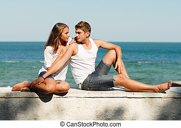Young happy couple embracing on sea coast - Young happy...