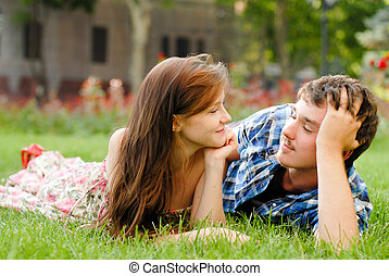 Happy young couple in love lying on green grass - Happy...