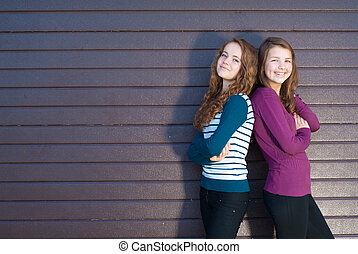 Friendship - Two best girlfriends against grey background -...