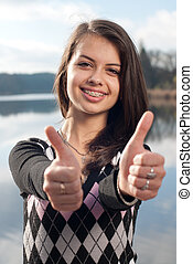 Smiling teenage girl picks up big thumbs up, against green...