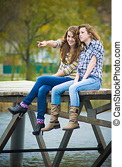 Two school girls sitting on river bridge - Two happy school...