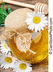 Pot of honey with daisies