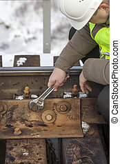 Railroad worker with wrench fix the nut on the bridge