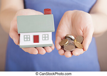 House sale - Little house toy and money in woman's hands