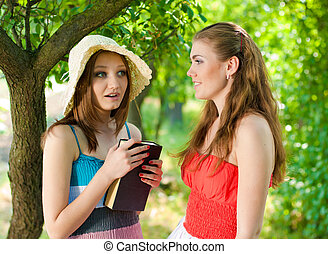 Two girls sharing impressions after reading book