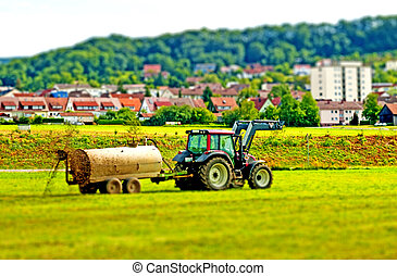 tilt-shift effect tractor with dung trailer