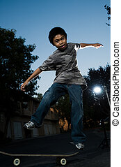 Young skate boarder - Young asian boy outside in the evening...