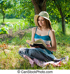 Young woman reading book in park on sunny day