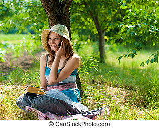 Young woman speaking on mobile in park on sunny day