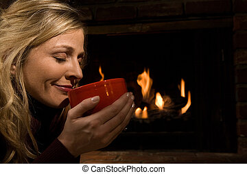 Soup or coffee by the fire - Attractive blond woman holding...