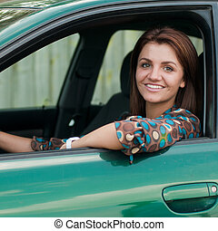 Happy young woman driving green car - Happy young beautiful...
