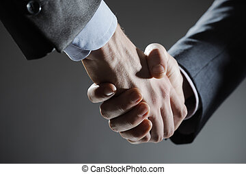 Business Deal - Two business men shaking hands, close up