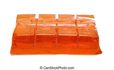 Block of orange jelly cubes on white background