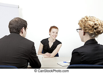 Young woman being interviewed for a job smiling as she...