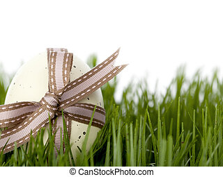 An Easter egg tied with ribbon in long grass - An Easter egg...