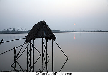 Modest straw hut of Indian fishermen in the Ganges,...
