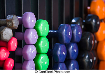 Dumbbells - Closeup of multicolored dumbbells on a rack in a...