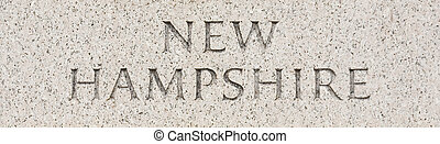 New Hampshire state name written in grey granite stone