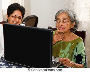 Elderly woman laptop - Indian mother and daughter surfing...