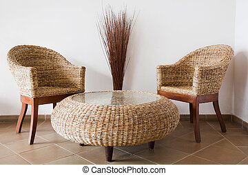 Rattan patio furniture against a white wall