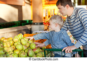 family at the market - father and his cheerful son choosing...