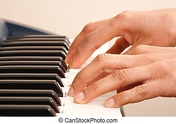 Playing keyboard - Closeup of a womans hands playing a piano...