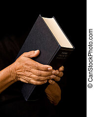 Old woman holding bible - An old woman holds a bible in...