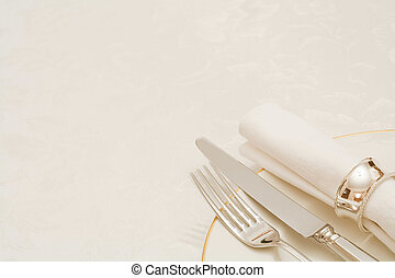 Knife and fork with napkin and plate, on a tablecloth with...