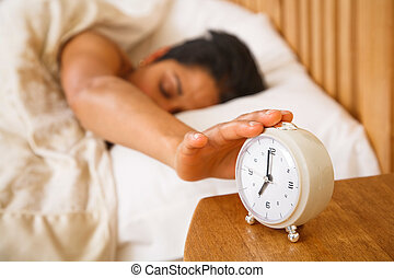 Woman waking up - An Indian Asian woman wakes up and reaches...