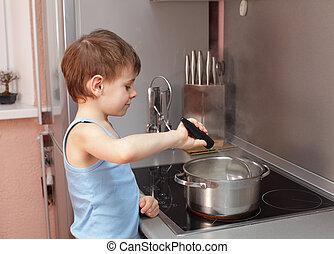 Child cooking porridge - Little boy cooking porridge in...