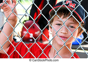 Youth baseball player in dugout - Upclose shot of a Little...