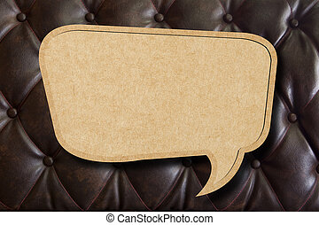 Recycle paper speech bubble on leather upholstery background