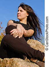 Attractive woman sitting on a rock - Low angle view of an...