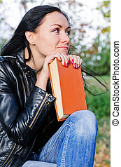Thoughtful woman with a book - Thoughtful woman sitting...