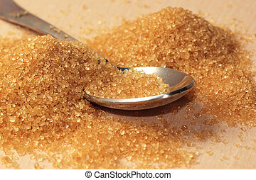 Raw brown sugar with a spoon - A pile of raw brown sugar...