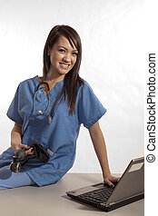 Young asian filipino nurse working on laptop