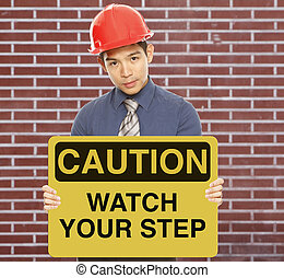 Watch Your Step - A man wearing a hardhat and holding a...