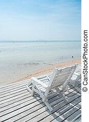 white beach chair facing ocean