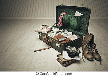 Packed Vintage Suitcase - Vintage suitcase open on a wood...